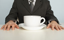 Huge cup of coffee on table near businessman Stock Photos