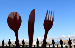 A huge cutlery sets in front of a city. Stock Photo