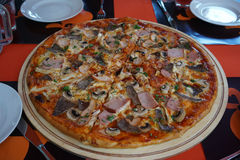 Huge delicious pizza. White plates Royalty Free Stock Photo
