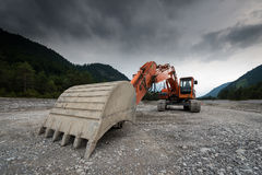 Huge digger. Perspective of digger power shovel in red on gravel royalty free stock photos