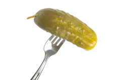 Huge dill pickle on a fork isolated on white Stock Images