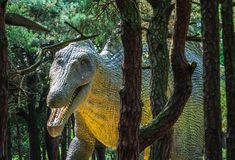 Huge dinosaur statue. Life sized huge dinosaur statue in a forest stock photography
