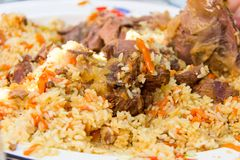A huge dish of fragrant pilaf in Kazakh with large pieces of lam stock photography
