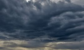 Huge evil clouds of dark blue-gray color with penetrating rays of sun stock photo