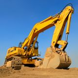 Huge excavator in front of cloudless sky. Heavy earth mover on a sunny day with the blue sky in the background stock photo