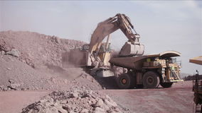 Huge Excavator. Mining. Loading of copper ore on very big dump-body truck stock video footage