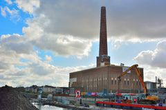 Huge factory chimney and Crane in action in The harbor of Ghent Royalty Free Stock Image