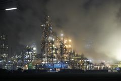 Huge factory fumes. Oil refinery surrounded with steaming fumes royalty free stock image