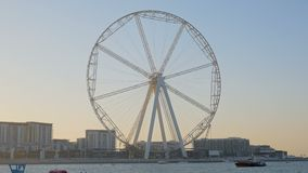 Huge Ferris wheel in Dubai in twilight, seagulls are flying in foreground, boats are floating. On Persian Gulf stock footage