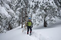Tired traveler, in snowshoes, drags an armful of firewood Stock Photo