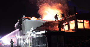 Huge fire blazing in commercial building. Firefighters on a roof stock footage