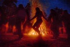 Pagan festival of Walpurgis night. Huge fire at night and young people around. Pagan festival of Walpurgis night: bonfires, dancing wildly, demons, witches. Folk Stock Image