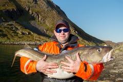 The huge fish. Cod. Hugs fisherman glasses Royalty Free Stock Photo