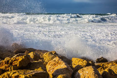 Huge foaming waves  beat against the shore rocks Stock Image
