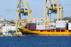 Huge freighter ship yellow downloading containers Stock Images