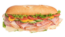 Huge freshly made sandwich on white background. Turkey breast, ham & cheese sandwich topped with fresh veggies isolated on white Stock Photos
