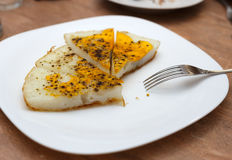 Huge fried ostrich egg cut into pieces on white plate. Horizontal side view Royalty Free Stock Photo