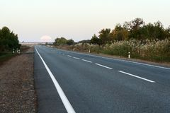 The full moon that leaves the horizon above the asphalt road in the early morning Stock Image