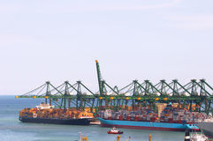 Huge gantry cranes and cargo container ships. Loading of cargo on/off container ships, image can be used to show a busy port, prosperity of a harbour royalty free stock photo
