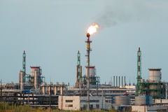 Huge gas and oil processing plant with burning torches, pipes and distillation of the complex.  Royalty Free Stock Image