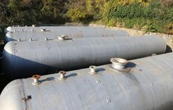 Huge gas storage tanks in an industrial area. Large cylinders are used to capture gas during energy crises or supply problems Stock Images