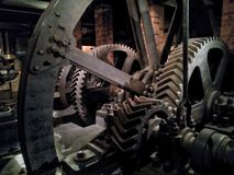 Huge gears mechanism of the old machinery. A part of steam powered retro machine with cogwheels in a dark interior Stock Images