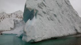 Huge giant iceberg in ocean of Antarctica. Glacier on background of snow mountains.Travel in calm cold polar north. Scenic blue water. Global warming. Unique stock video footage