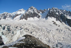 Huge glacier, snow and high rocky peaks of Caucasian mountains Stock Image