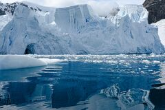 Glacier wall in Antarctica, majestic blue and white glacier edge reflecting in blue sea water, Paradise Bay, Antarctica