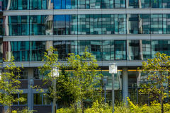 Huge glass building adorned by nearby trees. A huge building with reflective glass windows and trees nearby its vicinity Stock Photography