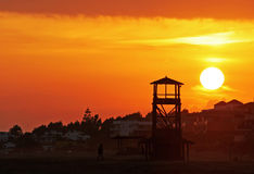Huge glowing golden sun sets behind a wooden lookout tower on a beautiful sandy beach in Spain. A golden orange sky and massive glowing yellow sunset at the end stock image