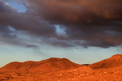 Huge gray and orange monsoon clouds over the Catalina mountains sunset in tucson arizona. Panoramic view of the Golden sunset Santa Catalina mountains covered in Royalty Free Stock Images