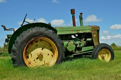 Huge green tractor parked in the field Stock Photos