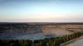 Huge grey mining quarry against small town silhouette