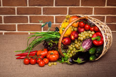 Huge group of fresh vegetables and fruits in wicker basket. On kitchen table, covered sack cloth on a background of a brick wall. Horizontal stock image