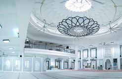 Huge hall of the mosque with modern minimalist chandelier at the center royalty free stock images