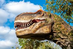 Huge head of a giant carnivorous dinosaur. The huge head of a giant carnivorous dinosaur among the autumn trees in the forest stock photos