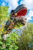 Huge head of a giant carnivorous dinosaur. The huge head of a giant carnivorous dinosaur among the autumn trees in the forest stock image