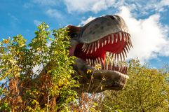 Huge head of a giant carnivorous dinosaur. The huge head of a giant carnivorous dinosaur surrounded by trees stock photography