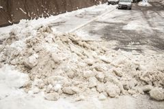 Huge heap of dirty snow and ice on a city street. Collected after heavy snowfall Royalty Free Stock Photography