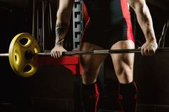 Huge heavily athlete approaches the bar in order to perform an e. Xercise called deadlift. Mixed media Royalty Free Stock Photos