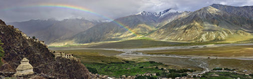 The huge high mountain valley after the rain, the big arc is bright rainbow through the gorge, in the foreground the white Buddhis Stock Photos