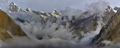 Huge high mountains the valley is shrouded in the morning mist: solid gray clouds lie along the valley, peaks with snow rise above Stock Image