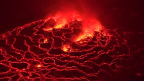Huge hot red melting lava lake erupting at Nyiragongo active volcano crater Congo Africa at night time in 4k aerial shot