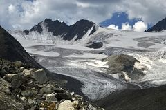 Huge ice field of the. Glacier at the foot of mount Iiktu, the main peaks of the South-Chuya ridge in the Altai mountains. Heavy snow clouds covered the sky Royalty Free Stock Image