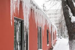 Huge icicles hanging from the roof stock image