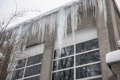 Huge icicles on the roof of the building.Deadly risk, danger to humans. Icicles hanging from the roof royalty free stock photo