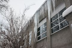 Huge icicles on the roof of the building.Deadly risk, danger to humans. Icicles hanging from the roof stock image