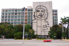 Huge image of Che Guevara in Plaza de la Revolucion. Havana, Cuba - March 12, 2018: a red classic car transits in front of the huge image of Ernesto Che Guevara Royalty Free Stock Photo