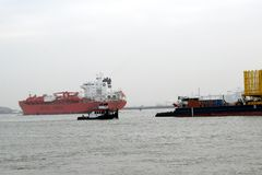 Sailing ships nearby the port of Rotterdam. Huge installation, intended for a drilling platform in the North Sea, is towed to the open sea by means of a tugboat stock images